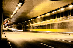 Night traffic on city streets. Vehicles getting in and out of the tunnel in motion blur Royalty Free Stock Image