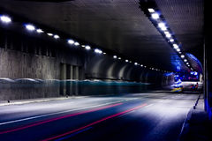 Night traffic on city streets. Vehicles getting in and out of the tunnel in motion blur Royalty Free Stock Photography