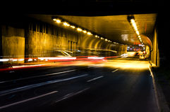 Night traffic on city streets. Vehicles getting in and out of the tunnel in motion blur Royalty Free Stock Photo
