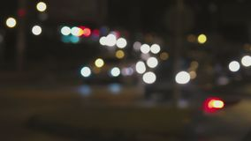 Night traffic lights. Defocused cars moving along in the light of carlights stock footage