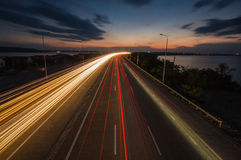 Night traffic lights on the highway. Last rays of sunset Royalty Free Stock Photos