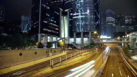 Night Traffic Near the Skyscrapers of Hong Kong City. Night in Hong Kong City. Movement of cars on a busy street surrounded by skyscrapers stock video