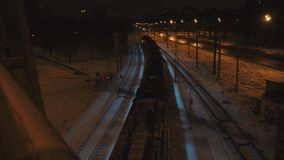 Night train goes under the bridge at winter. Electric train goes on rails under the bridge by the road with cars at winter night in the city of Saint Petersburg stock footage