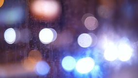 Night transport moving liight. Rain water drops on bus window glass stock video footage