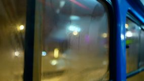 Night transport moving liight. Rain water drops on bus window glass stock footage