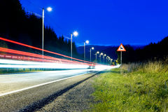 Night travel. Sign by the road at night with cars pasing by Stock Photos