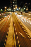 Night tunnel traffic. In sydney, blurred headlight trails, buildings in distance Stock Photo