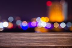 Night twilight blurred light bokeh in downtown bangkok empty of dark wood table abstract background for montage product display. Or design stock images