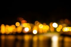 Night twilight blurred light gold bokeh reflecting on the sea surface water abstract background.  stock photos