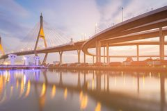 Night twilight suspension bridge and interchange highway. Reflection river front Stock Photography