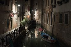 Night in Venice tine streets. Tiny street illuminated by streetlight with blue and red boats on the channel. Travelling picture Royalty Free Stock Photos