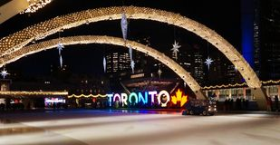 Night view across the brightly illuminated for New Year eve skating rink with TORONTO sign on the central Nathan