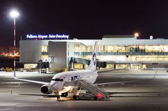Night view of the airport and the plane of the airline UTair. Russia, Saint-Petersburg April 2017. Royalty Free Stock Image
