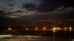 Airport at night. Plane boarding and taking off. Night view of the airport with terminal, plane with jet bridge and aircraft taking off stock video