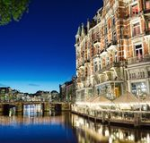 Night view of Amsterdam canal and Hotel De L `Europe building. Amsterdam, Holland - May 13, 2019: Night view of Amsterdam canal and Hotel De L `Europe building royalty free stock photo