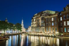 Night view of Amsterdam canal and Hotel De L `Europe building. Amsterdam, Holland - May 13, 2019: Night view of Amsterdam canal and Hotel De L `Europe building stock images