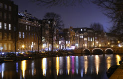 Night view of Amsterdam canals. The colorful reflections of the street lights in the water of the canals is typical of Amsterdam by night and well exemplified by Royalty Free Stock Photography