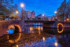 Amterdam canal, bridge and medieval houses in the evening. Night view of Amterdam cityscape with canal, bridge and medieval houses in the evening twilight Stock Images