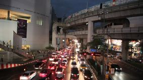 Night view of Bangkok downtown. Street Sukhumvit. Above street is BTS train passing. Bangkok is city with big problems with traffic congestion and air pollution stock video footage