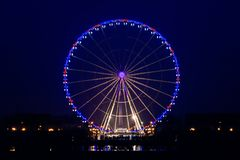Night view of big wheel in Paris. View of the illuminated and motionless Big wheel of the Place de la Concorde in Paris, France with the obelisk in the stock photo
