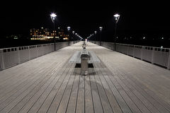 Night view of a  boardwalk, bench and lamp posts Stock Image