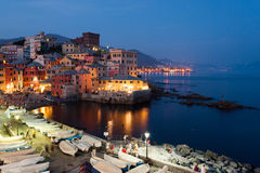 Night view of Boccadasse, a sea district of Genoa. Boccadasse, a sea district of Genoa famous for its typical colored houses, during a summer evening with people Stock Photos