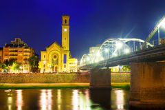 Night view of Bridge  over Ebro river and church in Tortosa Stock Photo