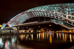 Night view of The Bridge of Peace over river Kura Stock Photos