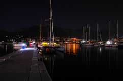 Night view of the catamaran and yacht. Montenegro. Night view of the catamaran and yacht on a background of mountains and city lights royalty free stock photos