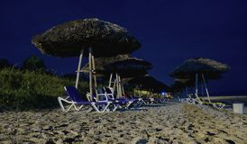 Night view of chairs and umbrellas royalty free stock photo