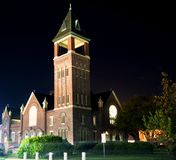 A night view of a church and bell tower. stock photos