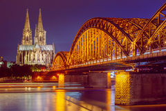 Night View Of Cologne Cathedral And Hohenzollern. Bridge, Germany. Europe. World Heritage - a Roman Catholic Gothic Cathedral. Toned, instant, filtered photo Stock Photography