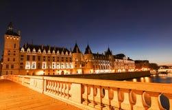 Night view of Conciergerie Castle and Bridge of Change -Pont au Change over river Seine. Paris, France stock image