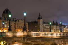Night view of Conciergerie Castle and Pont Notre-Dame bridge. Over river Seine. Castle Conciergerie is a former prison located on west of the Cite Island. Paris Stock Photography