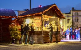 Night view on a craftsman`s cottage with walkers and illuminations of Christmas around Royalty Free Stock Image