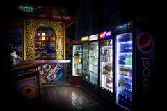 Night view of a customer at a small beverage outdoor shop with many refrigerators. royalty free stock photos