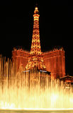 : Night view of the dancing fountains of Bellagio and the Eiffel Tower replica Stock Images