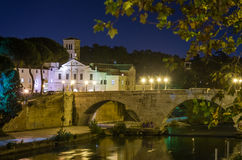 Night view of the dome of St. Bartholomew from the bridge on the lantern-lit promenade of the Tiber River in Rome, Italy autumn wa Royalty Free Stock Photography