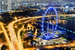 Night view of downtown with giant Ferris wheel, Singapore. Beautiful night view of downtown with giant Ferris wheel by Marina Bay in Singapore. Amazing cityscape royalty free stock photography