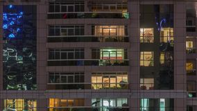 Night view of exterior apartment building timelapse. High rise skyscraper with blinking lights in windows. With people moving inside. Pan up stock video