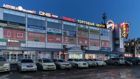 Night view of facade building of shopping center and cars parked in parking lot in front of store Stock Photo