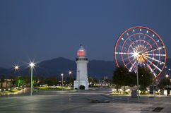 Night view of Ferris wheel and lighthouse in Batumi. Night View of Batumi with Ferris wheel and old lighthouse on the seafront over mountains, Black Sea, Georgia Royalty Free Stock Photo