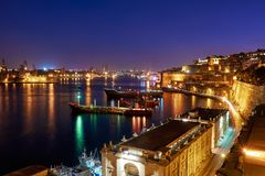 The night view of Grand Harbour with the cargo ships moored near. St. Barbara Bastion from the Lower Barrakka Gardens, Valletta Royalty Free Stock Images