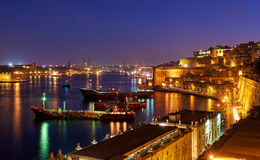 The night view of Grand Harbour with the cargo ships moored near Royalty Free Stock Photography