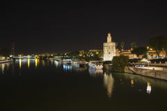 Night view of the Guadalquivir river in Seville, Spain. Gold Tower. Triana Bridge in the background stock image