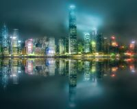 Skyline of Hong Kong in mist from Kowloon, China. Night view of Hong Kong skyline in mist from Kowloon with reflection on water, China Stock Photography