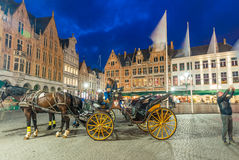 Night view of Horse Carriage in Bruges main square.  Royalty Free Stock Photography