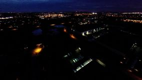 Night view of house lights, streets and buildings from in air flight above ground
