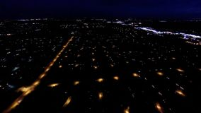 Night view of house lights, streets and buildings from in air flight above ground. Aerial night view of residential suburban neighborhood with street lights and stock video