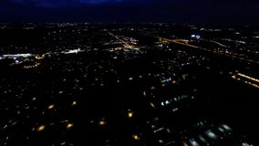 Night view of house lights, streets and buildings from in air flight above ground. Aerial night view of residential suburban neighborhood with street lights and stock video footage